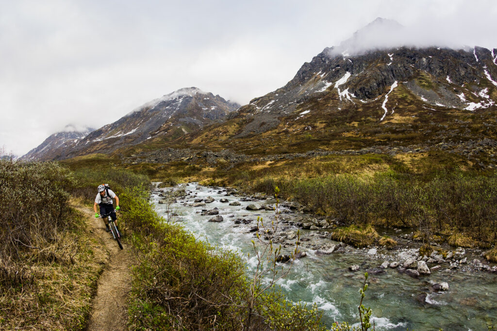 Man mountain biking on a singletrack trail, Alaska, US