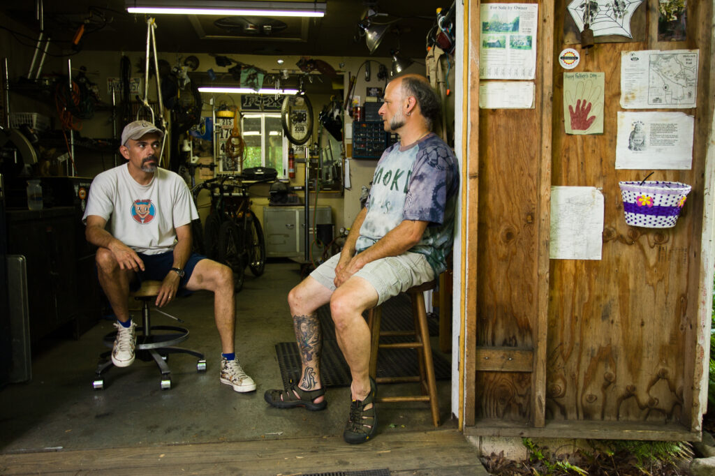 Two frame builders sit in their workshop, Ashelville, NC