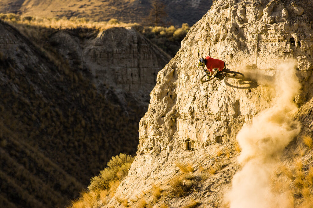 Man doing wall ride stunt on his mountain bike, Kamloops, BC