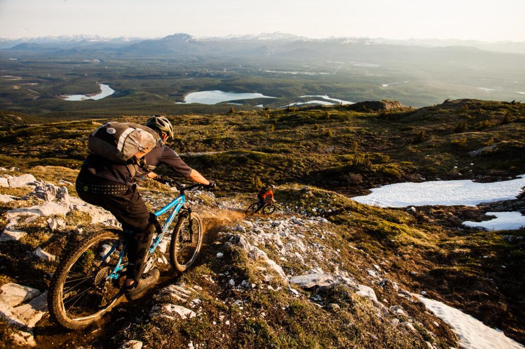 Two mountain bikers descend on singletrack trail, near Whitehorse, Yukon, Canada