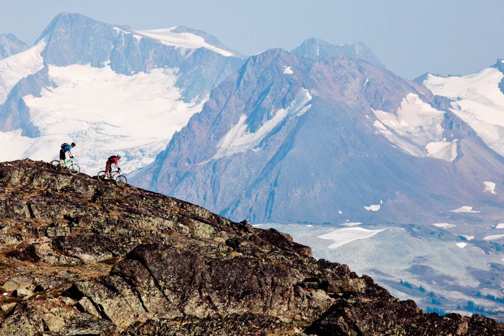 Two mountain bikers ride a ridgeline, in front of a glacier, Whistler, BC
