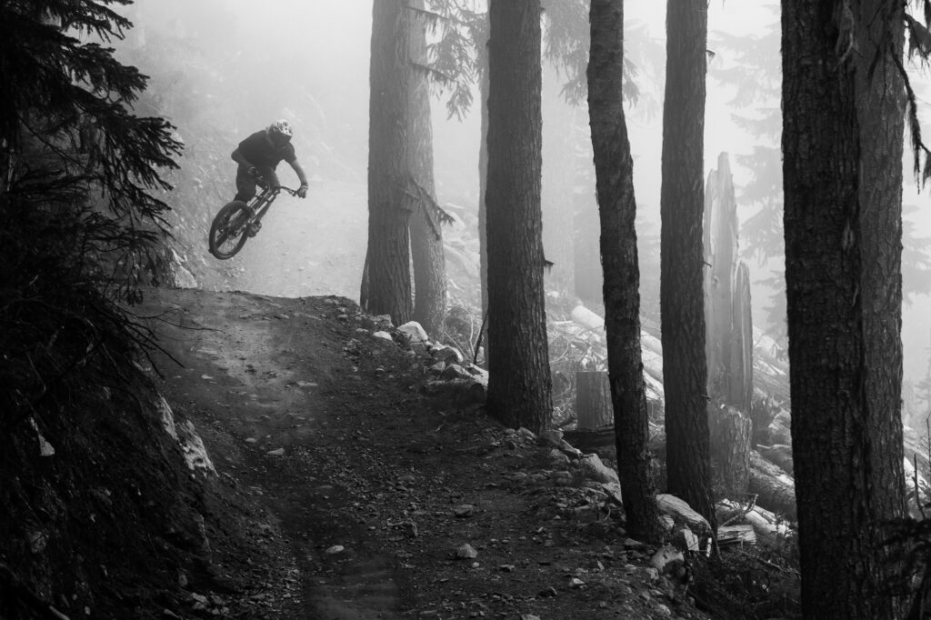 Mountain biker jumps out from fog, Whistler, BC