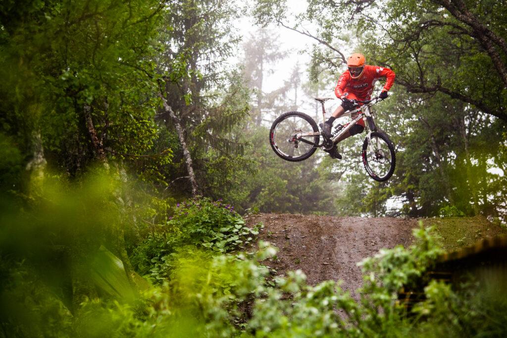 Mountain biker whips bike over tabletop jump, Åre, Sweden