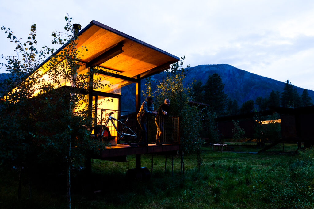 Two mountain bikers enjoy a beer on patio of cabin, Winthrop, WA