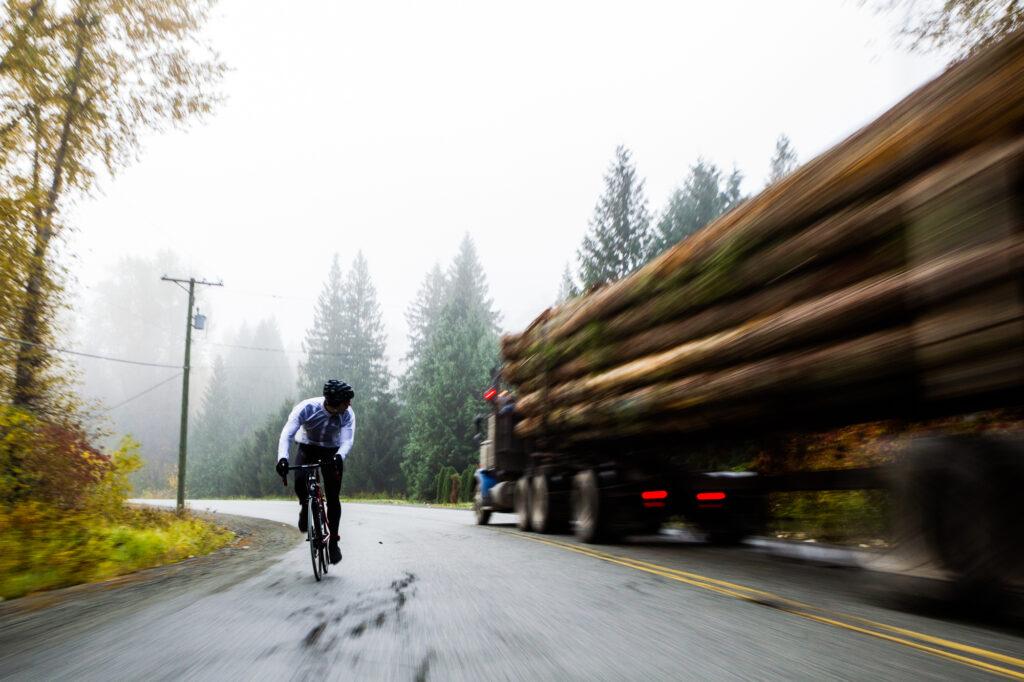 Road biker looks over shoulder at passing logging truck, Pemberton, BC, Canada