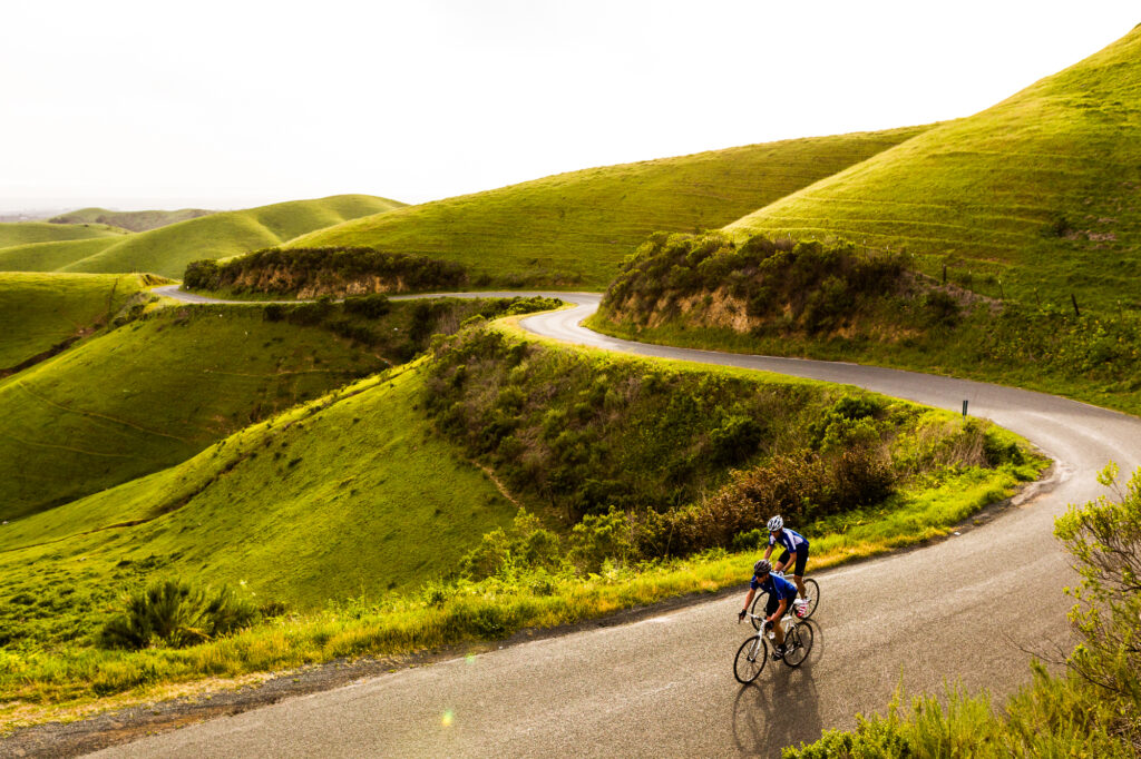 Two road riders climb up through green rolling hills, Salinas, CA