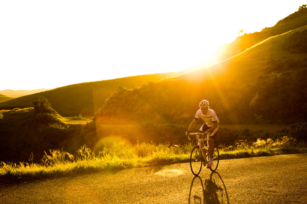 Road biker climbs up through grassy hills at sunset (backlit)